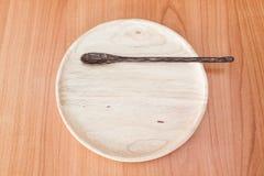 Piatto di legno sulla tavola di legno Immagini Stock