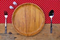 Piatto di legno, tovaglia, cucchiaio, forcella sul fondo della tavola immagini stock