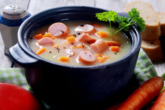 Piatto di minestra appetitoso sul vaso nero Fotografie Stock Libere da Diritti