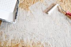 Piatto di Osb dipinto con pittura bianca con un rullo fotografie stock