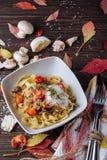 Piatto di pasta con carne ed i funghi su un fondo di legno Menu di autunno immagini stock libere da diritti