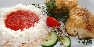 Piatto di pesce con riso e salsa al pomodoro fotografia stock