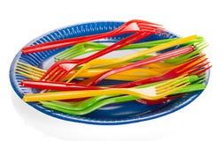 Piatto di plastica eliminabile e spine multicolori su bianco Fotografie Stock Libere da Diritti