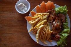 Piatto di pollo saporito con le patate fritte e l'insalata Carne arrostita sul modello di legno dell'insegna della tavola con il  immagine stock libera da diritti