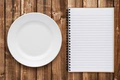 Piatto e libro di cucina vuoti fotografia stock libera da diritti