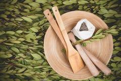 Piatto e pagaie di legno sul fondo delle foglie verdi fotografia stock libera da diritti