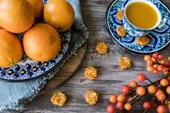 Piatto fatto a mano spagnolo blu con le arance, bacche, succo in tazza sulla tavola di legno fotografia stock libera da diritti