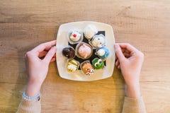 Piatto femminile della tenuta della mano con i dolci sotto forma di un animale Fotografia Stock