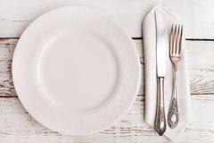 Piatto, forcella e coltello sulla tavola di legno bianca Fotografie Stock