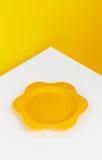 Piatto giallo sulla tavola bianca immagini stock