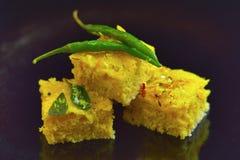 Piatto indiano di Dhokla con il peperoncino rosso su un fondo nero fotografia stock libera da diritti