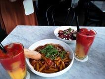 Piatto italiano delizioso - insalata rossa della pasta e della quinoa del penne della salsa e succhi freschi immagini stock