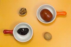 Piatto marinato della prugna in rosso Pomodori marinati in piatto arancio Fotografia Stock