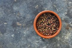 Piatto marrone rotondo dei granelli di pepe di Sichuan, destra del centro, su un fondo grigio fotografie stock libere da diritti