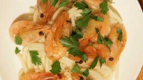 Piatto Mediterraneo degli spaghetti con i gamberetti Piatto dei prodotti puliti freschi e ecologici stock footage