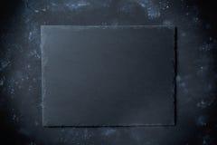 Piatto nero dell'ardesia su fondo di pietra con la vista superiore Fotografia Stock