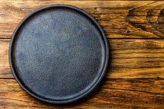 Piatto nero rustico vuoto del ghisa sopra vecchio fondo di legno fotografia stock