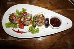 Piatto piacevolmente decorato della carne su un piatto del triangolo Fotografia Stock