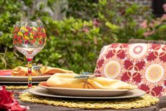 Piatto Pranzare-giallo del patio e vetro di vino dipinto a mano, intrattenere all'aperto immagine stock