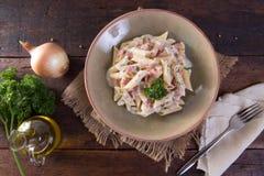Piatto regionale italiano fatto di pasta con l'ingrediente quale olio, cipolla, nepskin sulla tavola di legno con tela di sacco Fotografie Stock Libere da Diritti