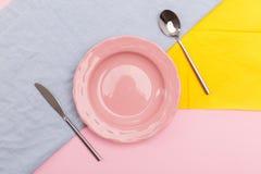 Piatto rosa sui tovaglioli colorati con la vista superiore della coltelleria Immagini Stock