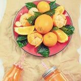 Piatto rosso con le arance e la bottiglia delle foglie verdi dei mandarini con succo sullo spazio leggero della copia di vista su fotografia stock libera da diritti