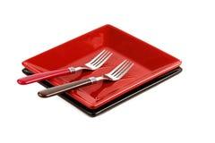 Piatto rosso e due forcelle su un bianco Immagine Stock