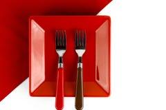 Piatto rosso e due forcelle su un rosso Fotografia Stock
