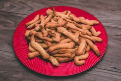 Piatto rosso in pieno dei biscotti sopra una tavola di legno Fotografia Stock Libera da Diritti