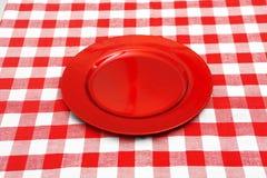 Piatto rosso sulla tovaglia rossa e bianca Immagine Stock