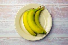 Piatto rotondo bianco con tre banane Fotografia Stock