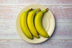 Piatto rotondo bianco con tre banane Immagine Stock