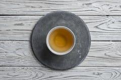 Piatto rotondo concreto grigio su fondo di legno leggero e una tazza di tè immagini stock