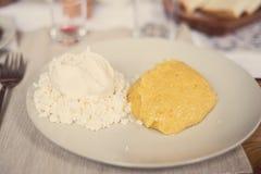 Piatto rumeno della polenta con formaggio e panna acida Immagini Stock