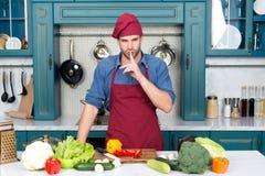 Piatto segreto del cuoco dell'uomo in cucina Cuoco unico con il dito di gesto di silenzio alla tavola con le verdure Ingredienti  Immagini Stock Libere da Diritti