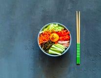 Piatto tradizionale di cucina coreana Bibimbap con manzo, le verdure e l'uovo su fondo blu fotografie stock libere da diritti