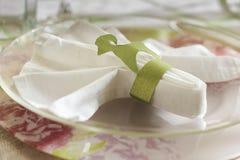 Piatto trasparente con un tovagliolo di tela bianco e un cardb verde Fotografia Stock