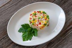 Piatto vegetariano: un piatto di riso bollito, di mais, dei piselli e dello swe fotografia stock