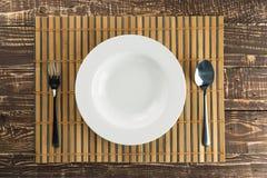 Piatto vuoto bianco su tessuto di bambù e sul fondo di legno della tavola Fotografie Stock