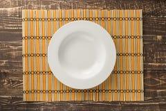 Piatto vuoto bianco su tessuto di bambù e sul fondo di legno della tavola dentro Fotografia Stock