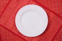 Piatto vuoto bianco su un rosso Immagini Stock Libere da Diritti