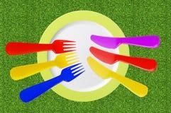 Piatto vuoto con i coltelli e le forcelle di colore su erba verde Fotografia Stock Libera da Diritti
