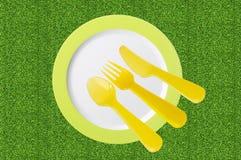 Piatto vuoto con i cucchiai e le forchette gialli su erba verde Immagini Stock Libere da Diritti