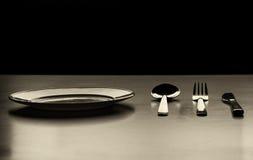 Piatto vuoto con il cucchiaio, il coltello e la forchetta su un fondo nero Fotografia Stock