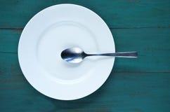 Piatto vuoto con il cucchiaio su fondo di legno Fotografia Stock Libera da Diritti