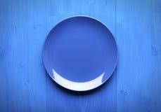Piatto vuoto sulla tavola blu fotografia stock