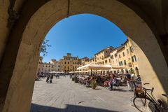 Piazza Anfiteatro - Lucca Tuscany Italy. LUCCA, ITALY - APRIL 16, 2017: Tourists and locals visit the ancient Town square Piazza dell`Anfiteatro - Amphitheater Royalty Free Stock Photos