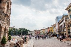 Piazza Bra and Arena di Verona urban view. Piazza Bra and Arena di Verona. Civilians are standing and talking in the middle of the street. Summer time and great royalty free stock photos
