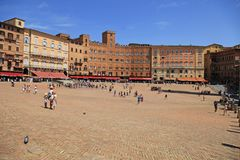 Piazza del Campo town square surrounded by historical buildings. SIENA, ITALY - JULY 21, 2017: Tourists on Piazza del Campo town square surrounded by historical Stock Photos