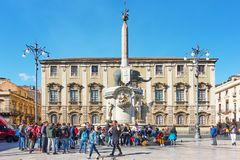 Piazza del Duomo and Fontana dell Elefante. Catania, Italy - March 15, 2019: People in Piazza del Duomo near Fontana dell Elefante - symbol of the city of royalty free stock images